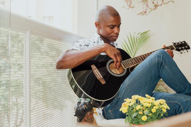 Primo piano di un giovane africano suonare la chitarra nel balcone