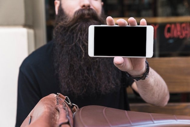 Primo piano di un giovane barbuto che mostra lo schermo del telefono cellulare