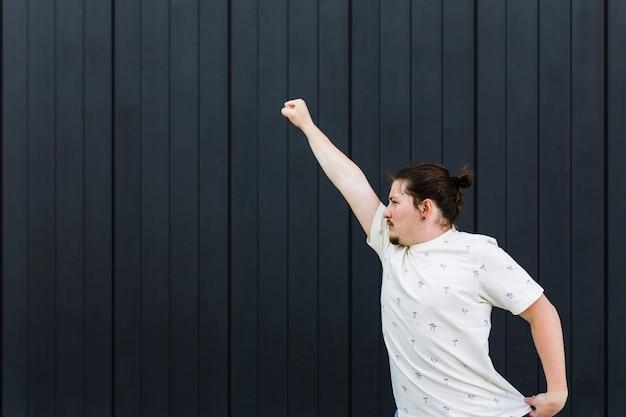 Primo piano di un giovane che alza le sue braccia contro il muro nero