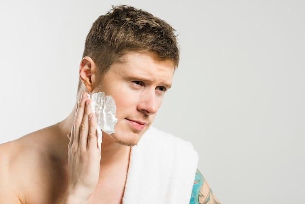 Primo piano di un giovane che applica schiuma da barba sulla sua guancia contro fondo grigio