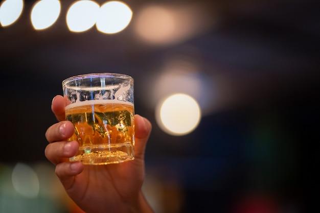 Primo piano di un giovane che tiene un bicchiere di vino su un bancone bar nel pub. la luce brilla sullo sfondo, degustazione di vini con spazio di copia.
