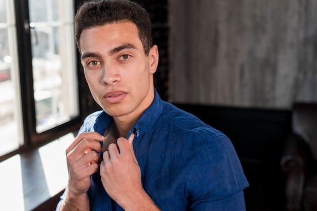 Primo piano di un giovane che tiene un colletto della camicia con la sua mano che guarda l'obbiettivo
