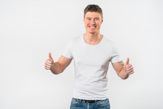 Primo piano di un giovane felice che mostra pollice sul segno contro sfondo bianco