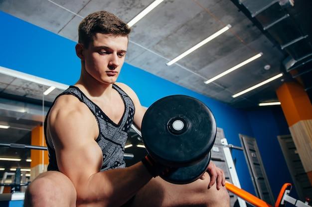 Primo piano di un giovane muscolare sollevamento pesi in palestra