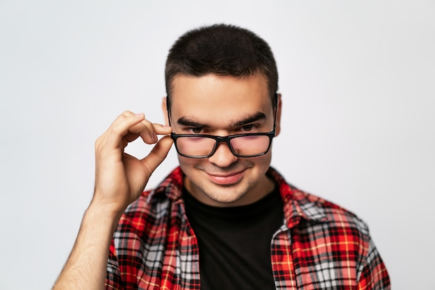 Primo piano di un giovane ragazzo alla moda con gli occhiali sorridente. un ritratto di un uomo intelligente in maglietta guardando attraverso nuovi occhiali