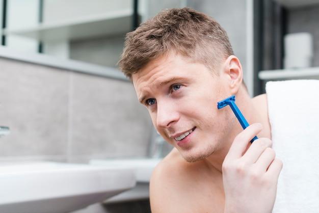 Primo piano di un giovane sorridente che si rade con il rasoio blu nel bagno