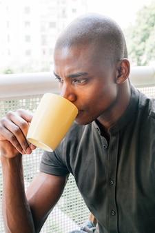 Primo piano di un giovane uomo africano rasato che beve il caffè
