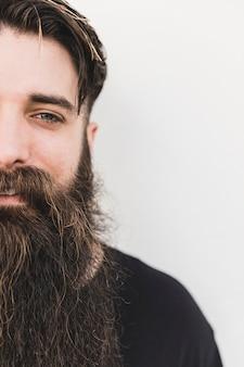 Primo piano di un giovane uomo barbuto sorridente