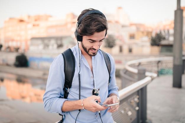 Primo piano di un giovane uomo che ascolta la musica su smartphone