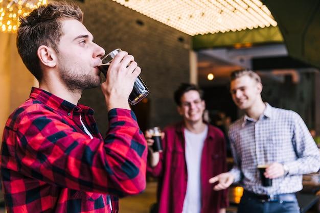 Primo piano di un giovane uomo che beve la birra nel ristorante pub