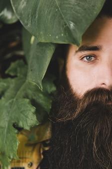 Primo piano di un giovane uomo con la barba lunga guardando fotocamera