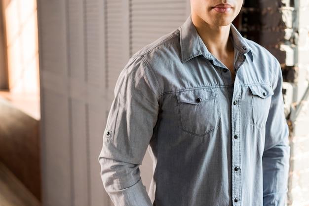 Primo piano di un giovane uomo in camicia di jeans blu