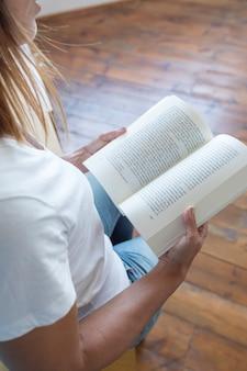 Primo piano di un lettore che legge un libro a casa
