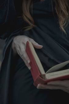 Primo piano di un libro rosso vintage tenuto dall'uomo