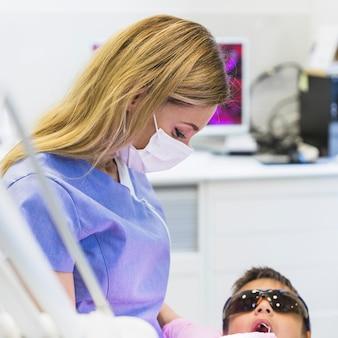 Primo piano di un medico femminile che controlla i denti del ragazzo