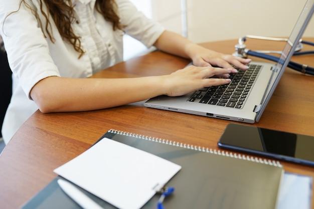 Primo piano di un medico femminile che scrive sul computer portatile