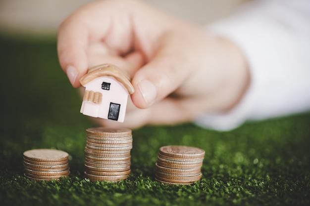 Primo piano di un modello di casa collocato sopra monete impilate