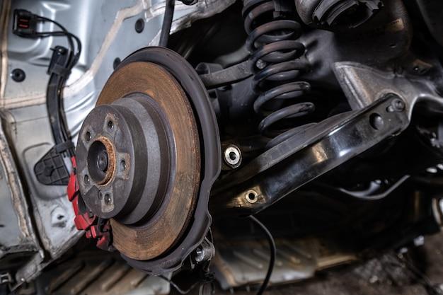 Primo piano di un mozzo auto, pinza freno, pastiglie freno, disco freno, cuscinetto ruota preparati per la riparazione. lavora nell'officina dei pneumatici