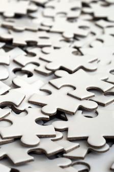 Primo piano di un mucchio di elementi incompleti di un puzzle bianco