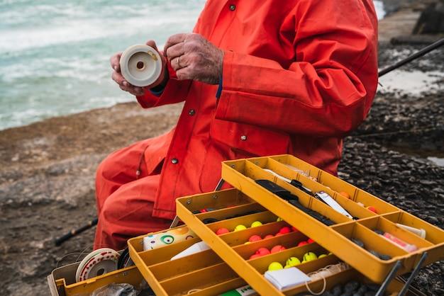 Primo piano di un pescatore che mette sull'esca con la scatola dell'attrezzatura di pesca. concetto di pesca e sport.
