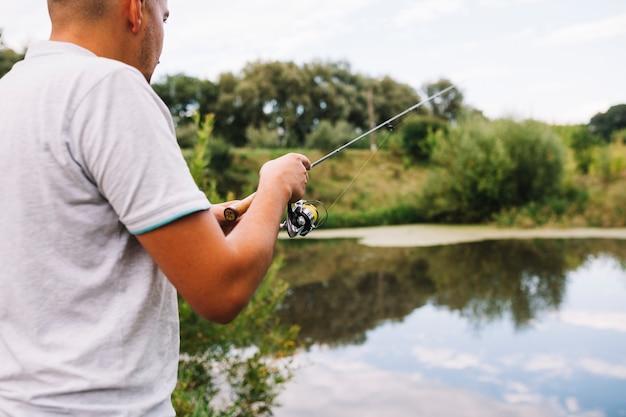 Primo piano di un pescatore che pesca sul lago