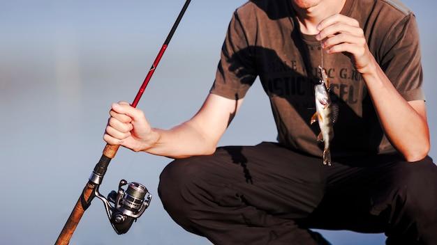 Primo piano di un pescatore con la cattura e la canna da pesca fresche