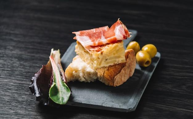 Primo piano di un piatto con alcuni tipici pincho de tortilla spagnoli e pincho de jamon