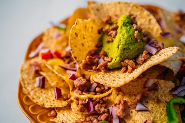Primo piano di un piatto di deliziosi chip di mais nachos tortilla con salsa di formaggio fuso, carne macinata, peperoni jalapeno, cipolla rossa, salsa e panna acida con salsa di guacamole. vista dall'alto