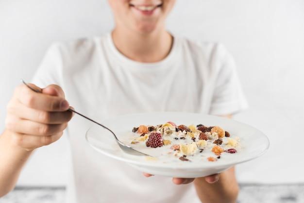 Primo piano di un piatto sorridente della tenuta del ragazzo del porridge e del cucchiaio della farina d'avena in mani