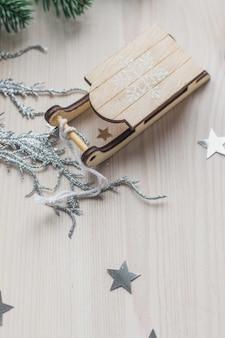 Primo piano di un piccolo ornamento di legno della slitta sul tavolo sotto le luci