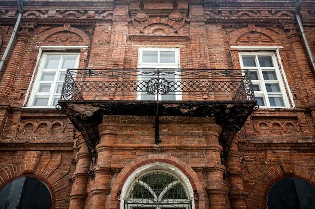 Primo piano di un portico in legno metallico con finestre bianche vecchie con una vecchia casa un palazzo fatto di mattoni vecchi