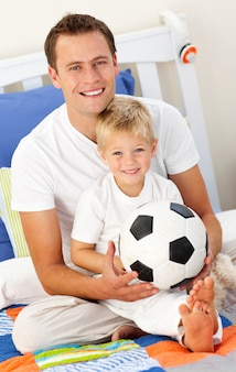 Primo piano di un ragazzino e suo padre giocando con un pallone da calcio