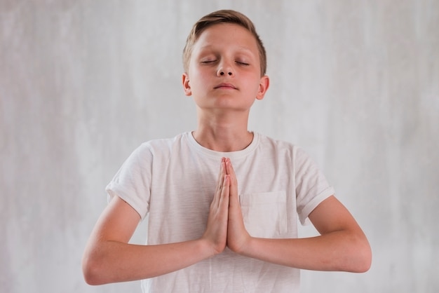 Primo piano di un ragazzo che chiude i suoi occhi facendo meditazione contro il muro di cemento