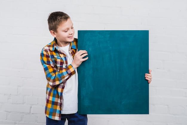 Primo piano di un ragazzo che esamina lavagna in bianco che si leva in piedi contro il muro di mattoni bianco