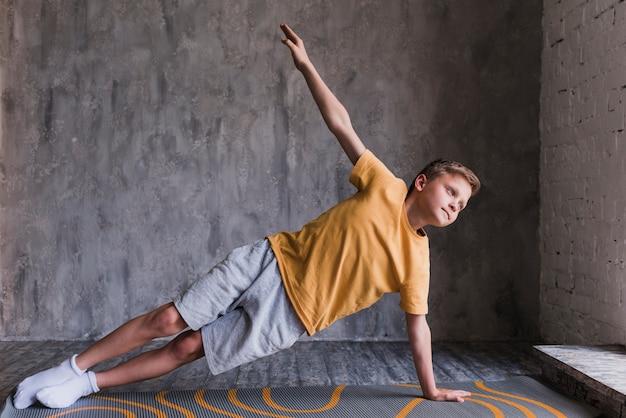 Primo piano di un ragazzo che fa allungando l'esercitazione contro il muro di cemento