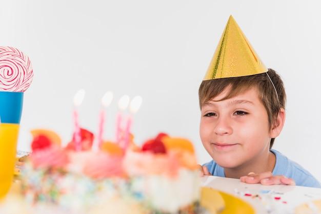 Primo piano di un ragazzo che guarda la sua torta di compleanno