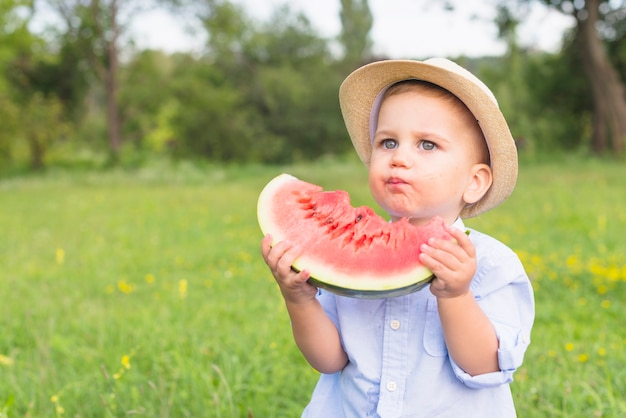 Primo piano di un ragazzo che mangia la fetta dell'anguria nel parco
