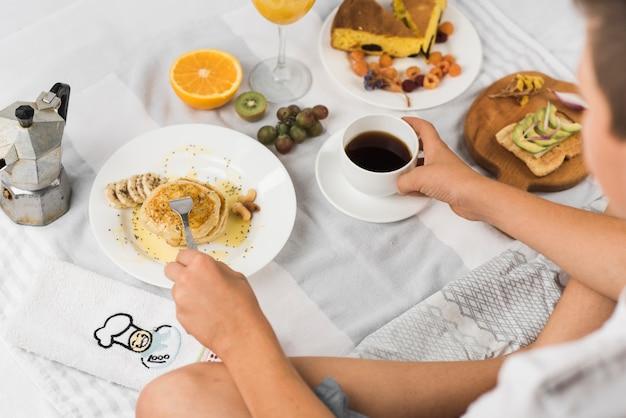 Primo piano di un ragazzo che mangia pancake e caffè sul letto