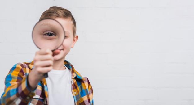 Primo piano di un ragazzo che osserva tramite la lente d'ingrandimento contro fondo bianco