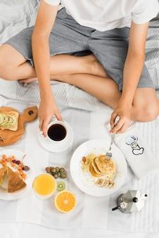 Primo piano di un ragazzo che si siede sul letto che mangia pancake e caffè