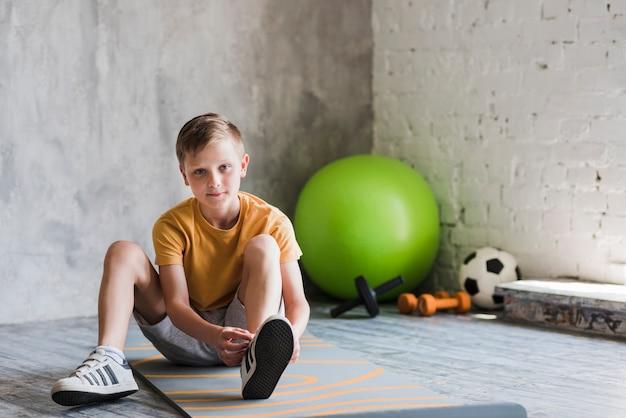Primo piano di un ragazzo che si siede sulla stuoia di esercizio che lega il pizzo di scarpa