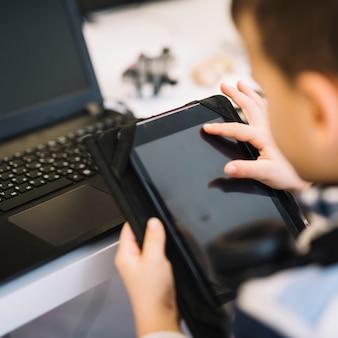 Primo piano di un ragazzo che tocca lo schermo della compressa digitale