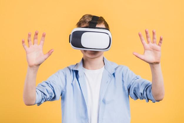 Primo piano di un ragazzo che usando con gli occhiali di protezione di realtà virtuale contro fondo giallo