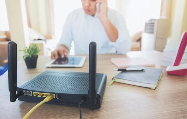 Primo piano di un router wireless e un uomo che utilizza smartphone sul salotto di casa ofiice, attrezzature per lavorare da casa,