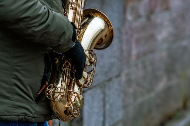 Primo piano di un sassofono nelle mani del musicista di strada
