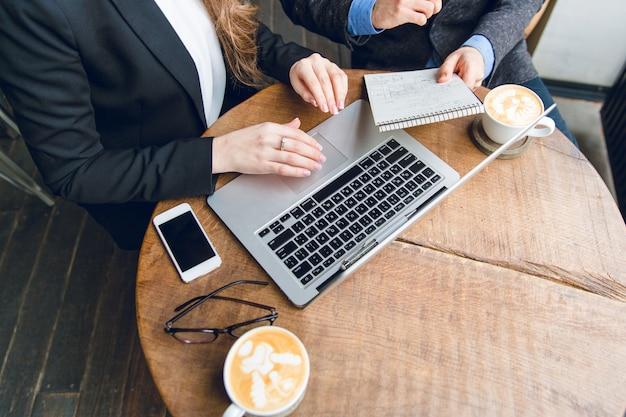 Primo piano di un tavolino da caffè con due colleghi seduti tenendo il taccuino e digitando sul computer portatile