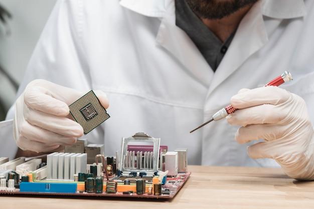 Primo piano di un tecnico maschio che inserisce chip nella scheda madre del computer