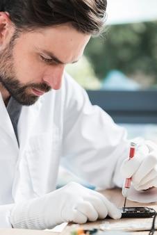 Primo piano di un tecnico maschio che ripara cellulare