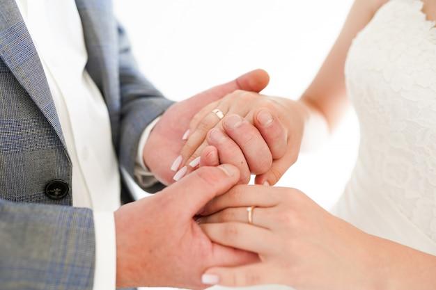 Primo piano di un tenersi per mano dello sposo e della sposa isolato