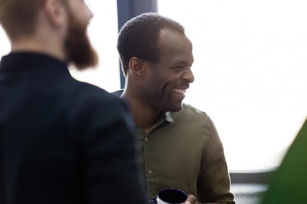 Primo piano di un uomo africano in piedi con i suoi colleghi